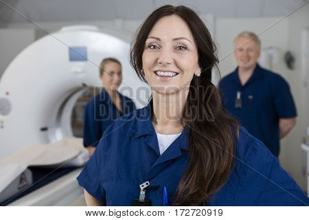Smiling Female Radiologist With Colleagues Standing By MRI Machi