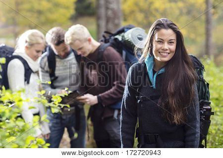 Happy Female Hiker With Friends Discussing In Background