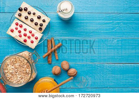 Granola in jar with berries, nuts and honey, healthy breakfast and diet concept, vitamin snack copy space background. Top view. Still life.