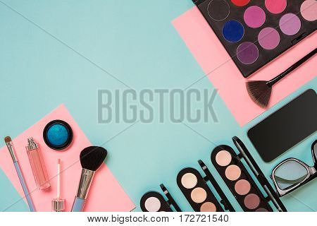Colorful cosmetics on blue workplace with copy space. Cosmetics make up artist objects: lipstick, eye shadows, powder, tools for make-up.Top view selective focus.