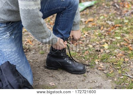 Male Hiker Tying Shoelace In Countryside