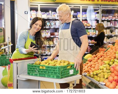 Worker Showing Digital Tablet To Colleague Working In Fruits Dep