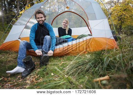 Man Wearing Boot While Woman Relaxing In Tent