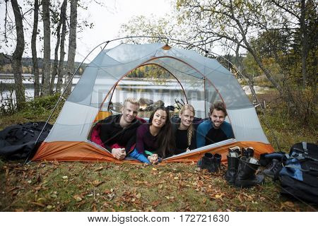 Smiling Young Friends Lying In Tent On Lakeshore