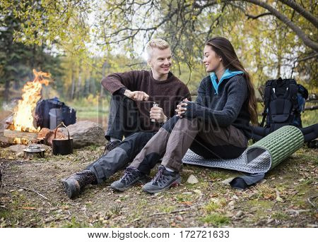 Man Grinding Coffee While Looking At Woman During Camping