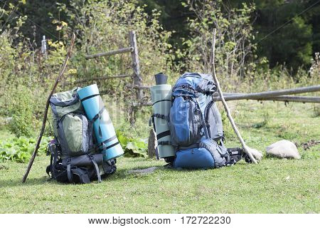 Two touristic hikers backpacks standing in a mountain valley on sunny day
