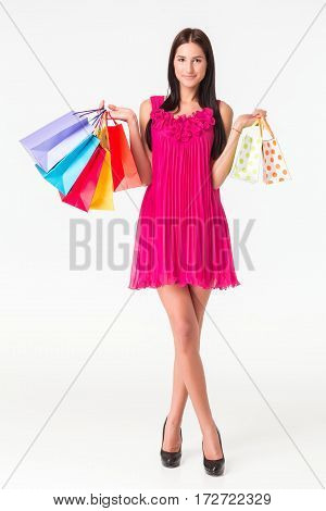 Happy young smiling woman with shopping bags after shopping. The brunette in a pink dress, isolated on white background