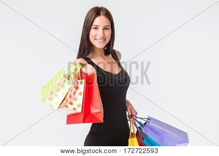Happy young smiling woman with shopping bags after shopping. The brunette in a black dress, isolated on white background