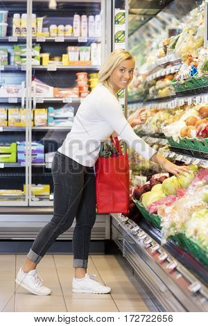 Young Woman Buying Cabbage In Supermarket