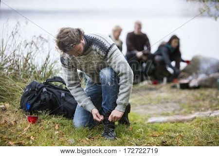 Hiking Male Tying Shoelace With Friends In Background