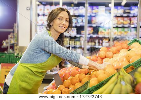 Smiling Saleswoman Arranging Oranges In Supermarket