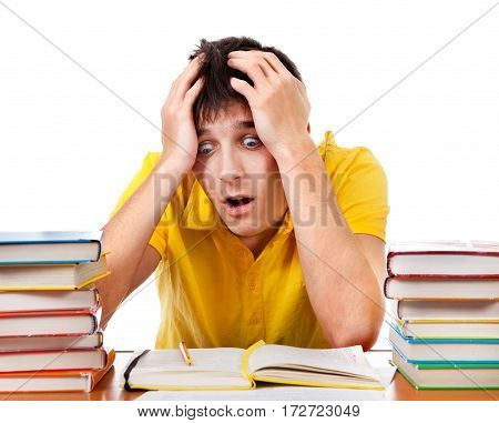 Surprised Young Man with the Books on the Desk Isolated on the White Background