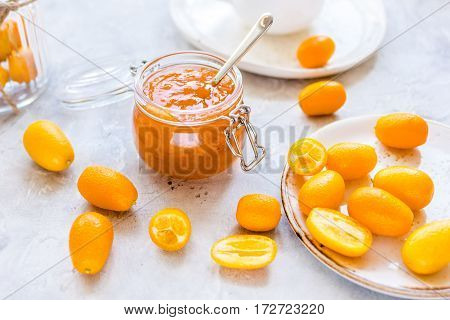 kumquat on plate and jam in jar at gray background.