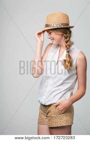 Side view of beautiful smiling woman summer woman in carefree stance holding hat brim feeling shy