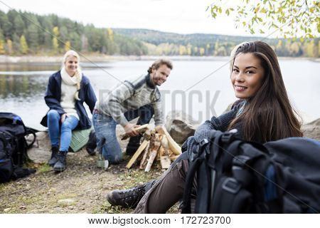 Woman With Friends Preparing Bonfire On Lakeshore