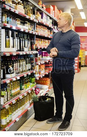 Man Wearing Smart Watch While Shopping At Grocery Store