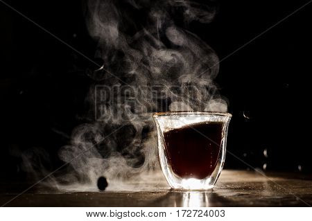 An illuminated coffee cup placed on the black background. Horizontal studio shot.