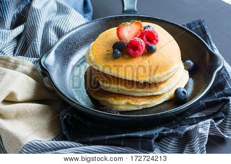Selective focus Pancakes with blueberries & raspberry on wood background