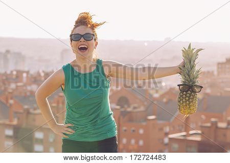joyfull young girl with glasses holding a pineapple