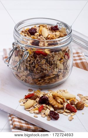 Jar of homemade muesli with nuts, berries, dried fruits, milk and honey on white background.Healthy breakfast. Top view