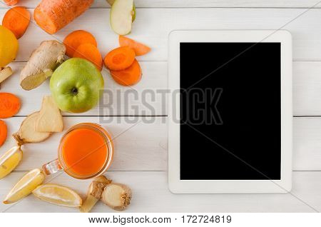 Order online detox cleanse drink, vegetable smoothie ingredients. Natural, healthy juice in glass jar. Carrot, apple, ginger and lemon mix on white wood with tablet screen for copy space, top view