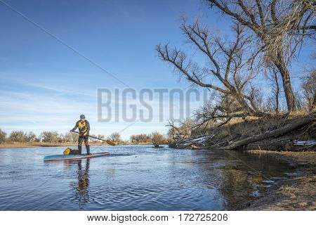 Expedition style winter stand up paddling on the South Platte RIver in eastern Colorado
