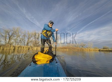 Senior male paddler on stand up paddleboard on a calm lake in Colorado, winter scenery without snow