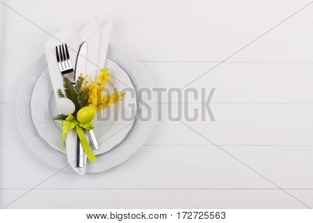 Easter dinner table setting on white wooden table, festive holiday background top view