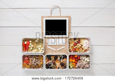 Healthy restaurant food, mockup for internet online order background. Fresh diet daily meals delivery. Vegetables, seafood, meat and fruits in foil. Top view, flat lay on wood, copy space on tablet
