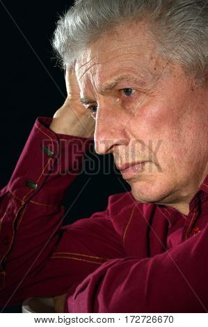 Portrait of a sad old man on a black background close-up