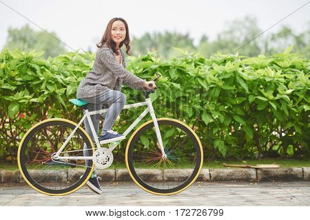 Portrait of pretty Vietnamese woman riding bicycle