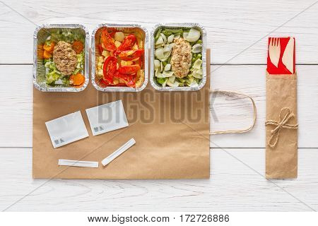 Healthy food delivery. Take away of natural organic fitness dishes for diet. Daily ratio meals in foil boxes on white wood. Craft package with smiley face, meat and salads. Top view, flat lay