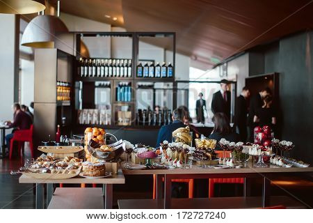 Assortment of different sweets: chocolate, mousse, fruit, cake, bananas, on holiday, on the background of people degradation restaurant, hotel
