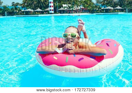 Tween girl relaxing on the inflatable ring in water in the aqua park in Thailand