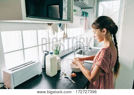 10 years old kid girl cooking in the kitchen, casual lifestyle photo series. Child making breakfast alone. Cozy homely scene.
