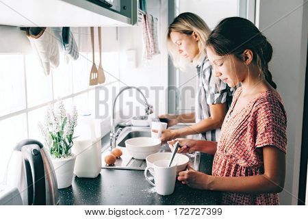Mother with her 10 years old kid girl cooking in the kitchen, casual lifestyle photo series. Child baking pie with parent together. Cozy homely scene.