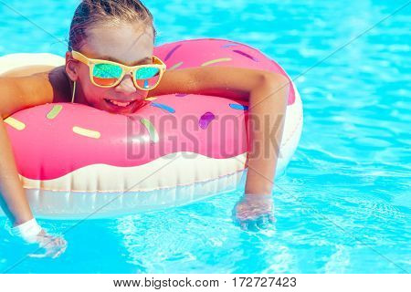 Tween girl relaxing on the donut lilo in resort pool in Thailand