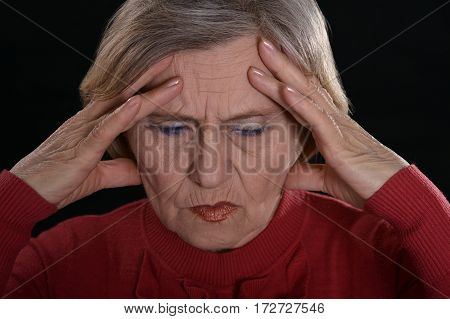 sad mature woman in red on a black background