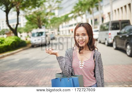 Lovely young Asian woman standing in the street with shopping bags