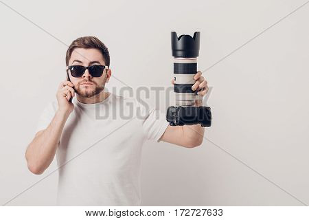 young professional photographer in a white shirt holds a heavy digital camera with a long lens and talking on the phone with a client. soft light