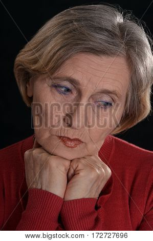 sad old woman in red on a black background