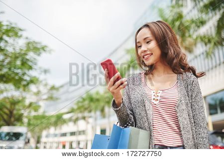 Lovely smiling Vietnamese woman reading message on her smartphone