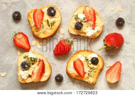 Toast with cream cheese with fresh berries strawberries blueberries almond flakes thyme
