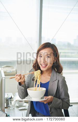Portrait of pretty Vietnamese business woman eating noddles with chopsticks