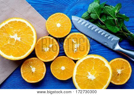 homemade orange and mint smoothie making on blue wooden table background top view