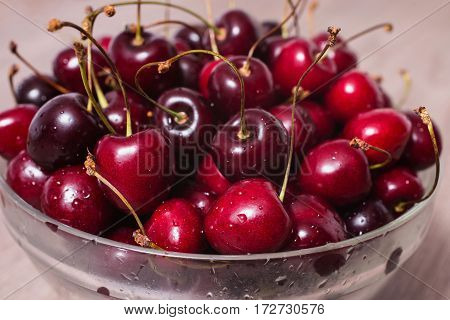Ripe juicy red cherry with drops of water in a transparent plate on a wooden background.