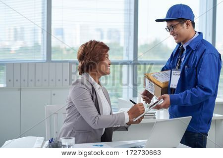 Smiling mature business lady signing for package