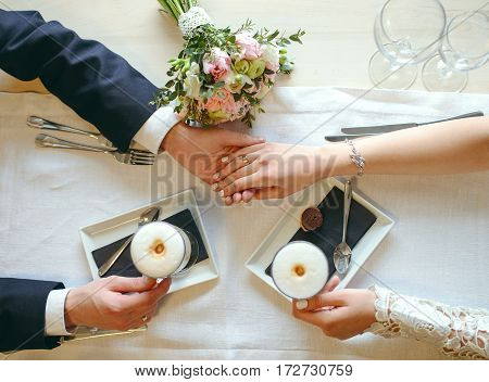 Close-up shot of hands. Groom holds bride's hand at the table at cafe. Top view
