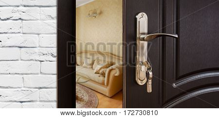 Half opened door handle closeup, entrance to a living room. View of sofa. Welcome, privacy concept. Door lock with keys, white brick wall, modern interior design.