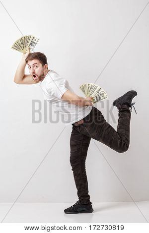 young handsome smiling man with a beard in a white shirt holding a lot of hundred-dollar bills and fooling around. money